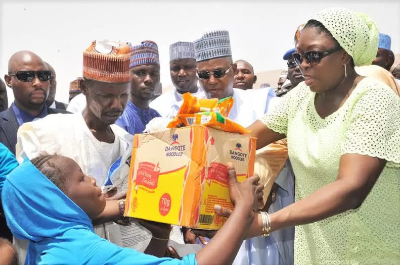 M.D. Dangote Foundation, Zouera Youssoufou, (Right)Presenting Food Items to one of The Beneficiary with his Farther(Left) While Borno State Governor (Middle) Alhaji Kashim Shettima, AtThe Distribution of Dangote Foundation Donate Foods Items for Ramadanto (IDP) Internal Displays People of Bakkasi Camp in Maiduguri BornoState. on 13-06-2016